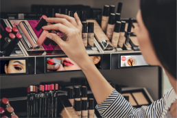 Woman holding make up with hand in front of eye level shelf media products on make up shelf.